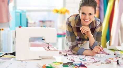 A lady in a checked shirt, sitting beside a white sewing machine at a table full of materials, buttons and thread