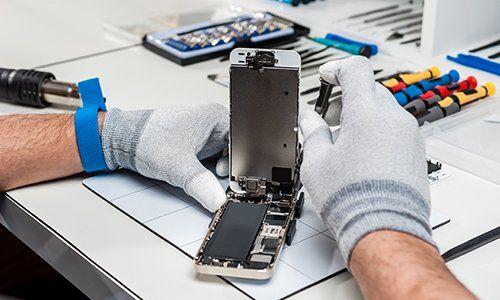 due mani con dei guanti che con un cacciavite riparano un telefono