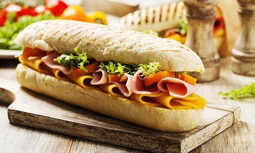 un panino con prosciutto,formaggio e insalata su un tagliere