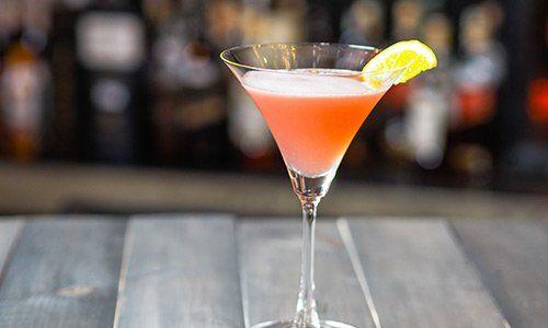 un bicchiere con un cocktail arancione e una fetta di limone