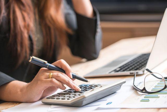 Primo piano di ragioniere femminile o calcoli banchiere fare