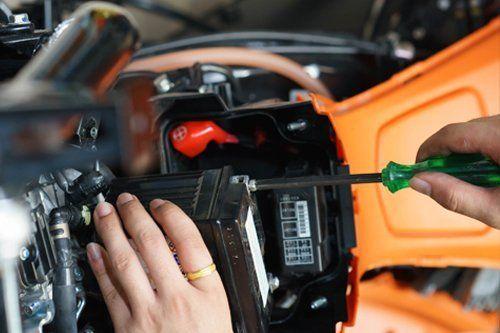mani con chiave inglese mentre riparano la batteria di un auto