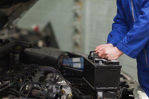 meccanico mentre prende in mano una batteria