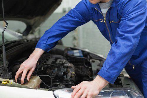 meccanico mentre sostituisce la batteria di un auto