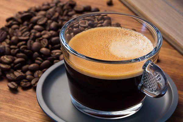 una tazza di caffè e accanto dei chicchi