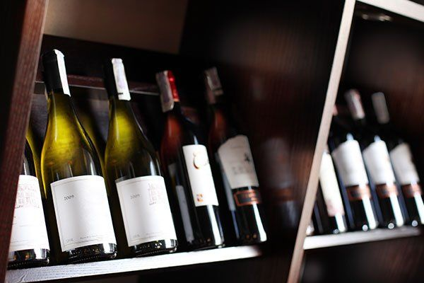 delle bottiglie di vino dentro a uno scaffale di legno