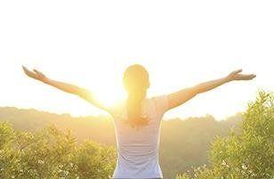 Donna aprendo le braccia al sole