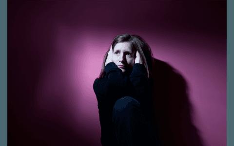 Giovane donna spaventata coprendosi delle orecchie