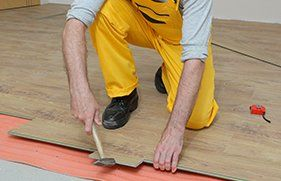 Male worker installing laminate floor, floating wood tile