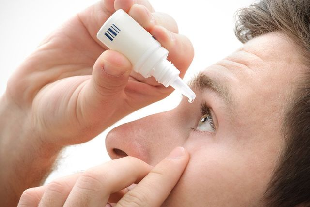 A man applying eyedrops