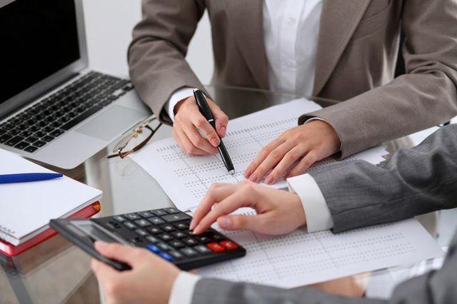 un uomo che con una penna indica un foglio e un altro che usa una calcolatrice