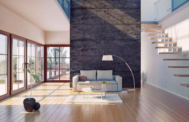 soggiorno open space con divano in mezzo alla stanza e vetrate