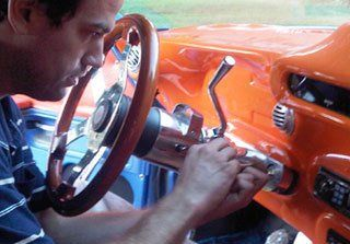 Mobile locksmith making a new key for a car.