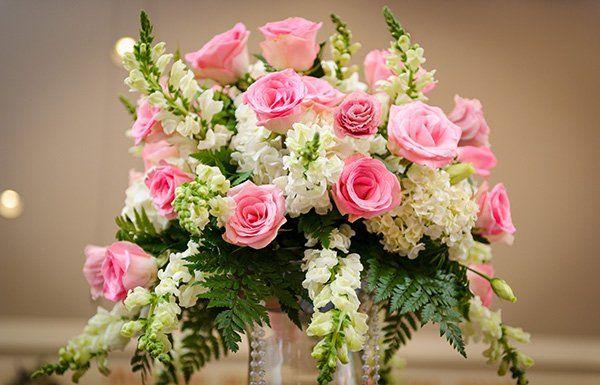 Delicato ornamento da tavola con rose rose e mimose bianche con un tocco di verde helecho