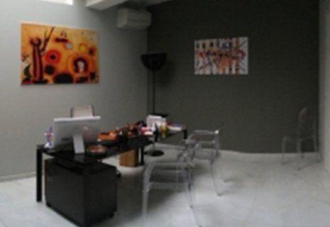 immagine dello studio con scrivania nera e quadri colorati