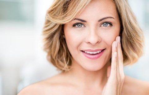 una donna con capelli corti  mentre sorride con una mano sulla guancia