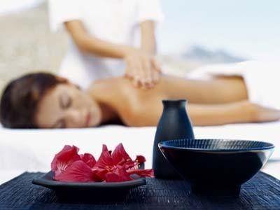 Un'estetista mentre fa un massaggio ad una donna sdraiata con la pancia in giù