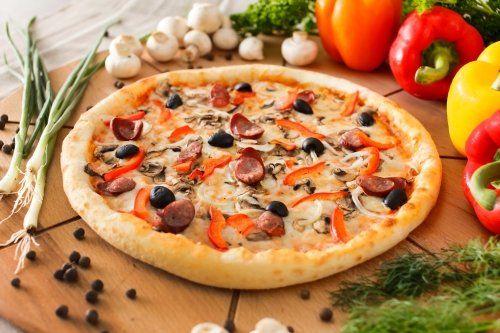 una pizza con wurstel, olive nere, funghi e della verdura accanto