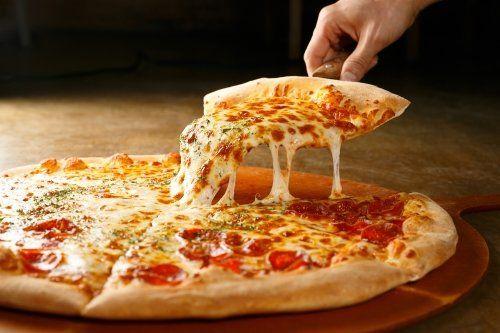 una mano che prende una fetta di pizza