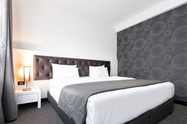 Moderno dormitorio in toni grigi e bianchi dove si ha installato il sistema di climatizzazione invisibile