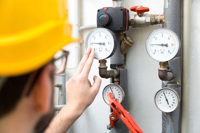 Operaio controllando le valvole di pressione del sistema