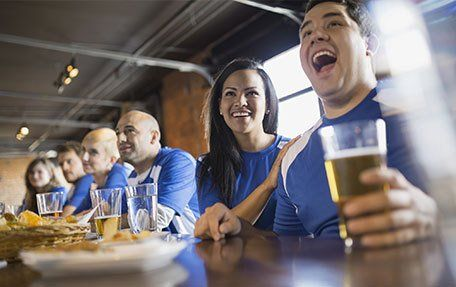 People in blue football shirts drinking at a bar