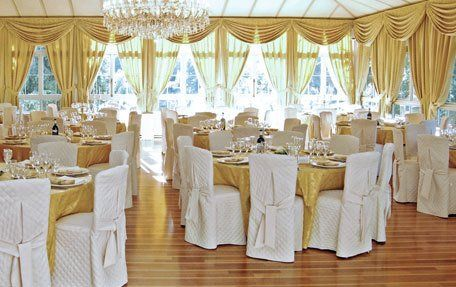 Large room set up for a wedding reception with cream and gold theme, and chairs covered with white material and sashes