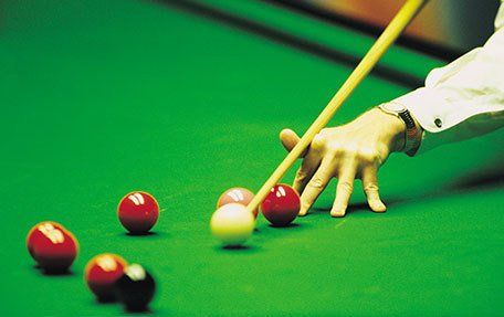 A snooker player taking aim