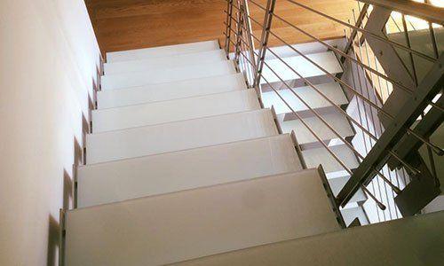 degli scalini in marmo bianco e sulla destra un corrimano in acciaio