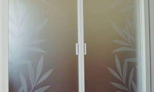 una porta in vetro a due ante con fiori bianchi disegnati