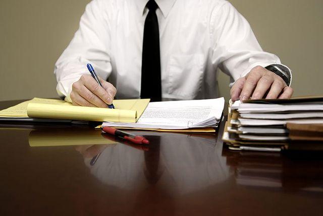 Un uomo elaborando il progetto di un documento e al suo fianco , vari documenti e cartelle impilati