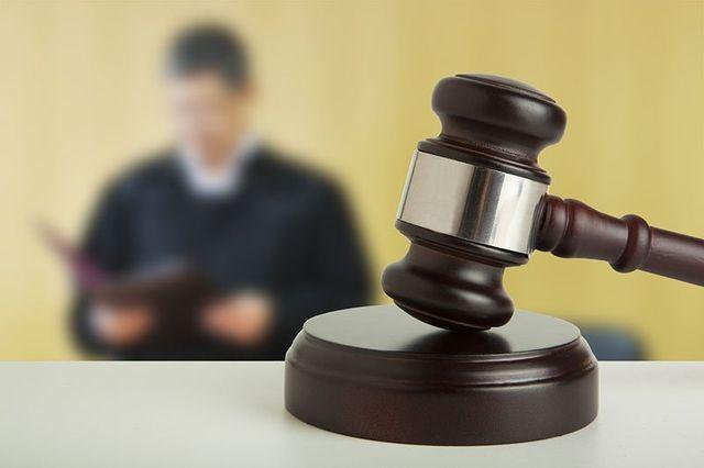 Un martello di giustizia e dietro una persona scialba