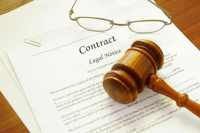 Un contratto,un paio di occhiali e un martello di giustizia