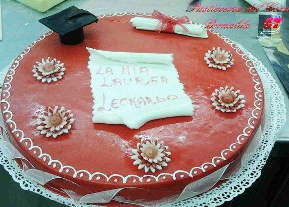 torta ricoperta di glassa rossa con margherite e dei ricami bianchi attorno e al centro una scritta
