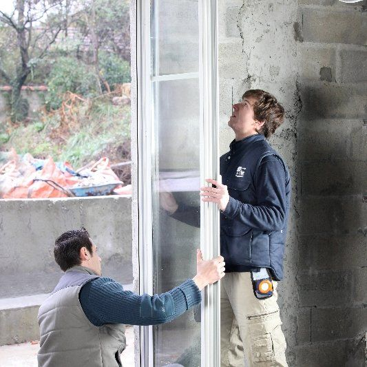 Two workmen installing a glass door