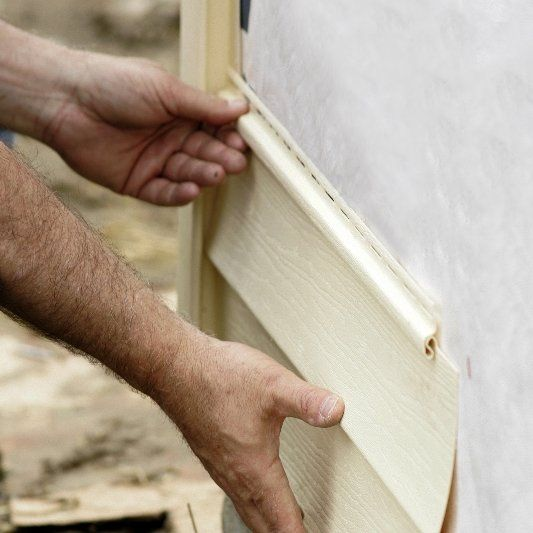 Workman's hands applying siding to side of house