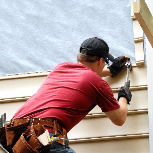 Workman using hammer to apply siding to house