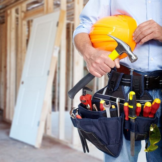 A workman with a tool belt and a hammer
