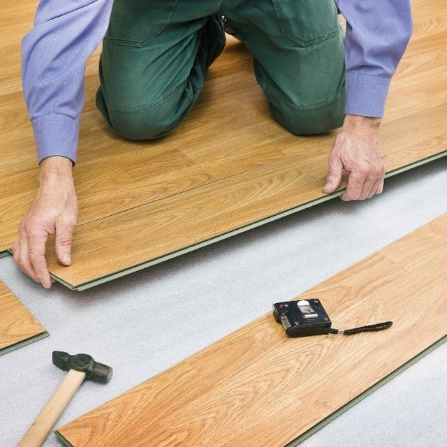 A workman lays new wood flooring