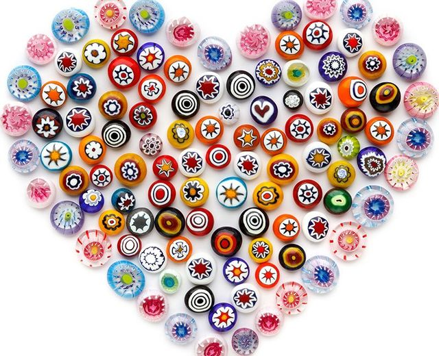 delle palline in vetro di diversi color e disegni disposte in modo tale da formare un cuore