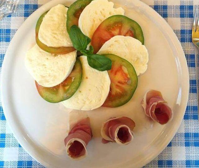 un piatto di formaggio, fette di pomodoro e dei salumi