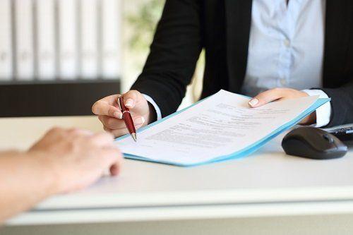 Uomo alla scrivania con una penna e dei documenti