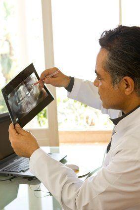 dentist examining an x-ray - South Texas Periodontal Associates