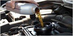 mano mentre versa olio nel bocchettone di un auto