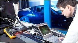 meccanico consulta un computer sopra un cofano di un auto aperto