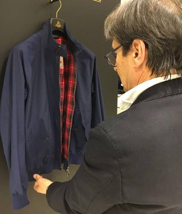 una mano di un uomo che tocca una giacca di color blu