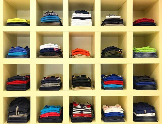 delle mensole con delle magliette di vari colori