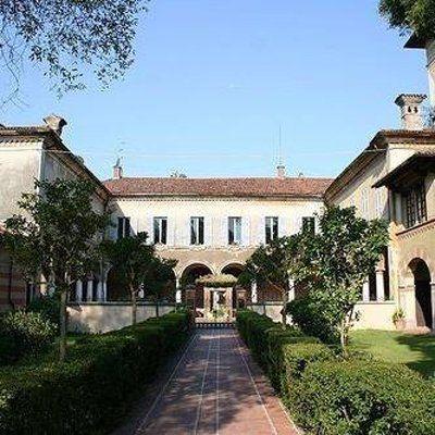 una corte con un giardino curato davanti a una villa italiana