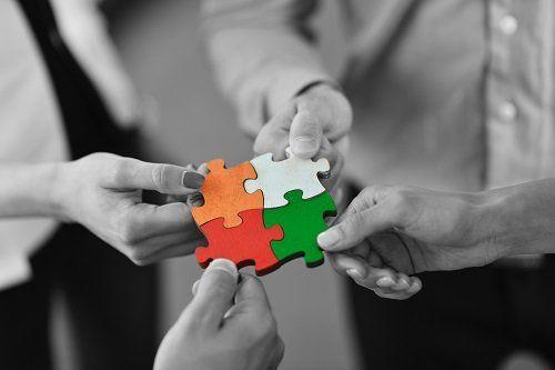 delle mani con in mano dei pezzi di puzzle