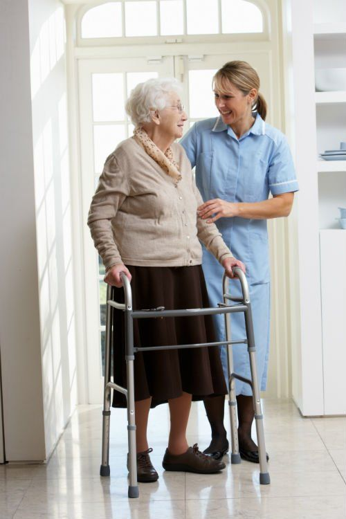 accanto una on camice di color azzurro una signora anziana con un deambulatore e